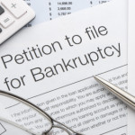 Close up of bankruptcy petition with calculator and pen